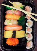 Takeout Sushi. Assorted Nigiri Sushi And A Yellowtail And Scallion Sushi Roll With Chopsticks In A T poster
