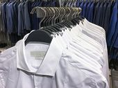 Clothes hang on a shelf . Cloth Hangers with d Shirt, suits. Mens business clothes poster