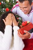 stock photo of christmas-present  - young couple are giving each other christmas presents - JPG
