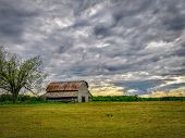 An Old Wooden Barn Next To A Big Tree Out On A Farm At Sundown With Dramatic Cumulus Clouds In High  poster