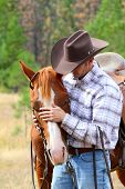 stock photo of western saddle  - Cowboy working his horse in the field - JPG