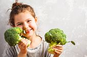 Little Beautiful Girl Eating Broccoli. Healthy Vegan Baby Foods Concept. poster