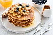 Stack Of Pancakes With Banana, Blueberries, Walnuts, Honey And Caramel Sauce On White Plate. Closeup poster