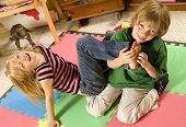 foto of tickle  - Adorable twins tickling each other on the playroom floor - JPG