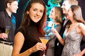 foto of party people  - Attractive woman enjoying a cocktail while a party - JPG