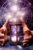 image of fortune-teller  - female hands holding houglass over background with zodiac - JPG