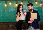 School Rules Concept. Man With Beard Hold Book And Sexy Girl Teacher Holds Alarm Clock, Chalkboard O poster