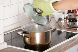stock photo of boiling water  - Young woman boiling something in pot  - JPG