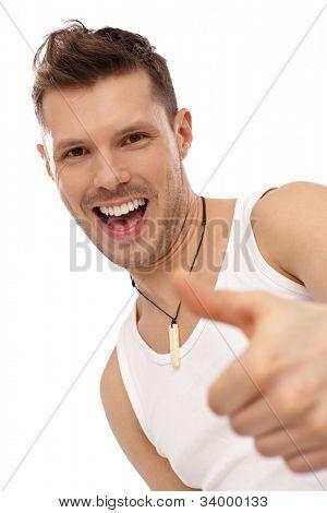 Retrato de jovem feliz sucesso mostrando o polegar acima, vestindo camiseta. Sim.