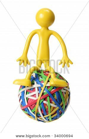 Miniature Figure Sitting on Rubberband Ball