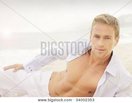 Successful young good-looking guy on the beach with relaxed open shirt