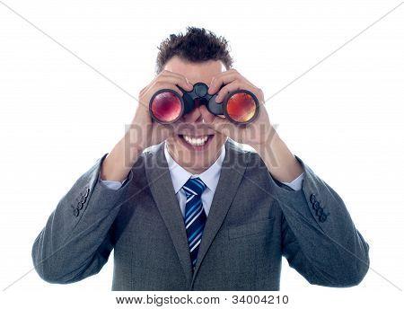 Smiling Businessman Looks Through Binoculars