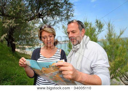 Pareja Senior de vacaciones mirando el mapa de la ciudad
