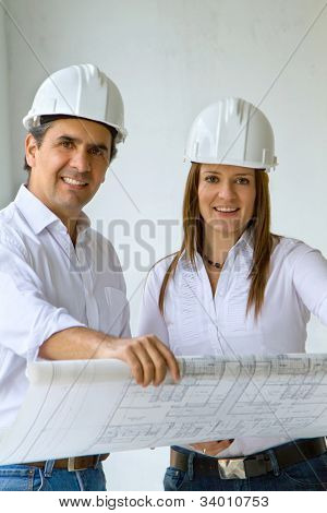 Architects at a construction site holding at blueprints and smiling
