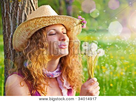 sweet girl in a meadow full of dandelions