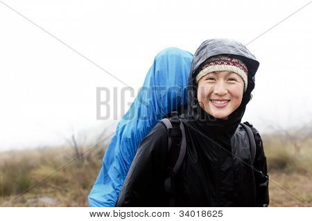 portrait of asian hiker with waterproof gear and backpack in the rain while trekking on an adventure expedition in the mountains during bad weather, cold and miserable