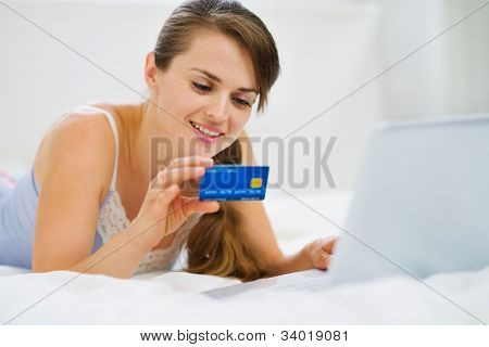 Happy Woman Laying On Bed With Laptop And Shopping On Net
