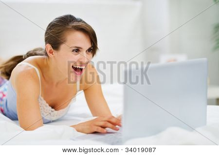 Woman Laying On Bed And Suprisely Looking In Laptop