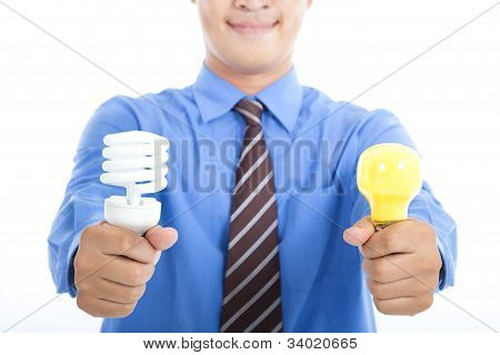 smiling businessman holding energy saving light bulb and tradition light bulb
