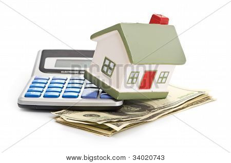 A model house sitting with a calculator and dollar