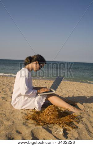 Mujer sentada en la playa con Laptop
