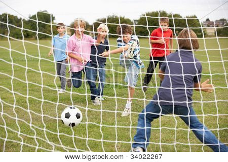 Boys playing soccer in park