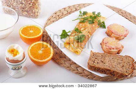 breakfast meal with a cheese omelet, boiled egg, oranges and ham and cheese toasts