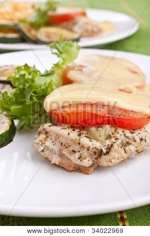 two servings of chicken breast french style roasted with tomatoes and cheese