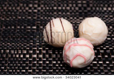 Three White Chocolates On Dark Cloth