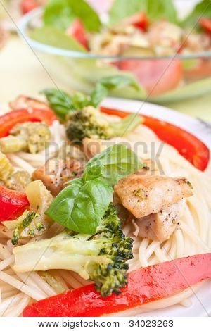 chicken and broccoli pasta dijon with bowl of salad at the back
