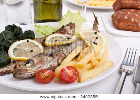 serving of grilled Blue whiting fish with lemon, pepper and fried spinach