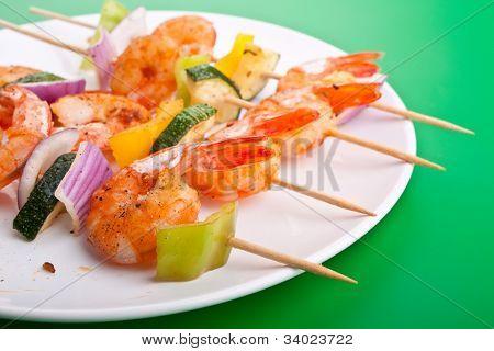 colores vegetales y brocheta de camarones a la plancha sobre fondo verde
