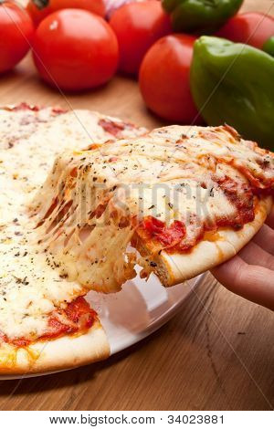 Slice of pizza margarita being removed from whole pizza with tomatoes in background