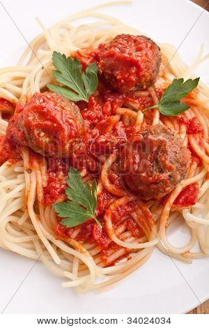 three meatballs with tomato sauce, spaghetti and parsley