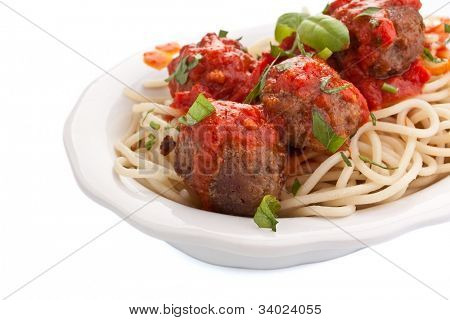 bowl of spaghetti with meatballs in tomato sauce and basil