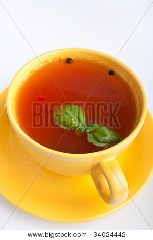 tomato soup in yellow cup on white background