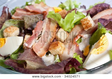 close up of caesar salad with bacon and eggs