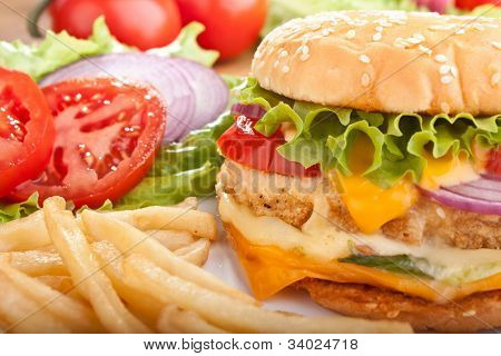 delicious cheeseburger with melted cheese and french fries and ingredients
