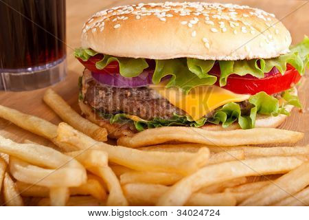 delicious cheeseburger with french fries and a drink