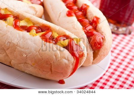 group of hot dogs and drink on checked table-cloth table