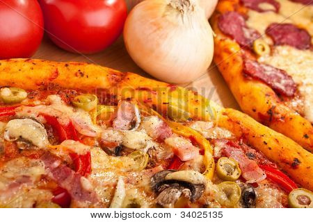 ham, mushroom and olive pizza and salami pizza at the back