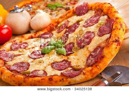 putting salami and green olives pizza on a table