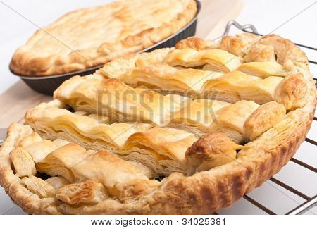 two pies - closed pie on a wooden board and open on a metal railing
