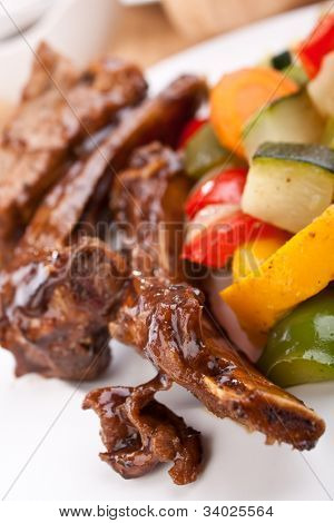 barbecue spare ribs on a plate with vegetables