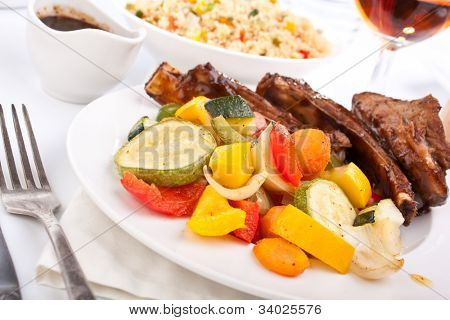 barbecue spare ribs on a plate with vegetables and couscous