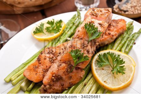 healthy salmon with coriander garnished with asparagus and lemon