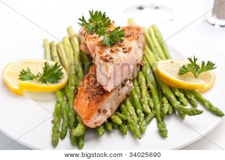 healthy salmon with coriander garnished with asparagus on white plate