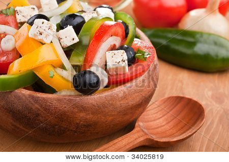close up healthy greek salad in a wooden bowl
