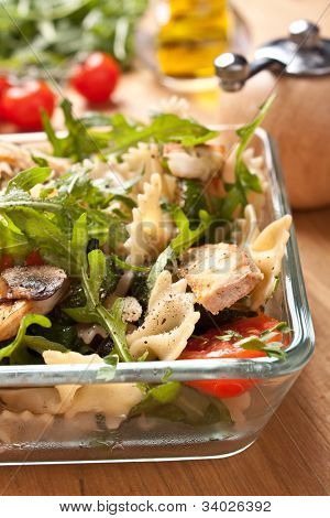 Serving of pasta,  turkey, mushroom, rocket and  tomatoes salad