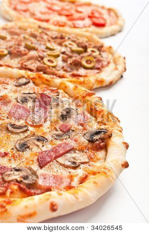 three different kinds of pizza in a row